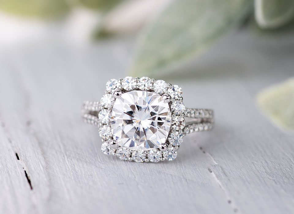 A cushion cut moissanite engagement ring with halo setting