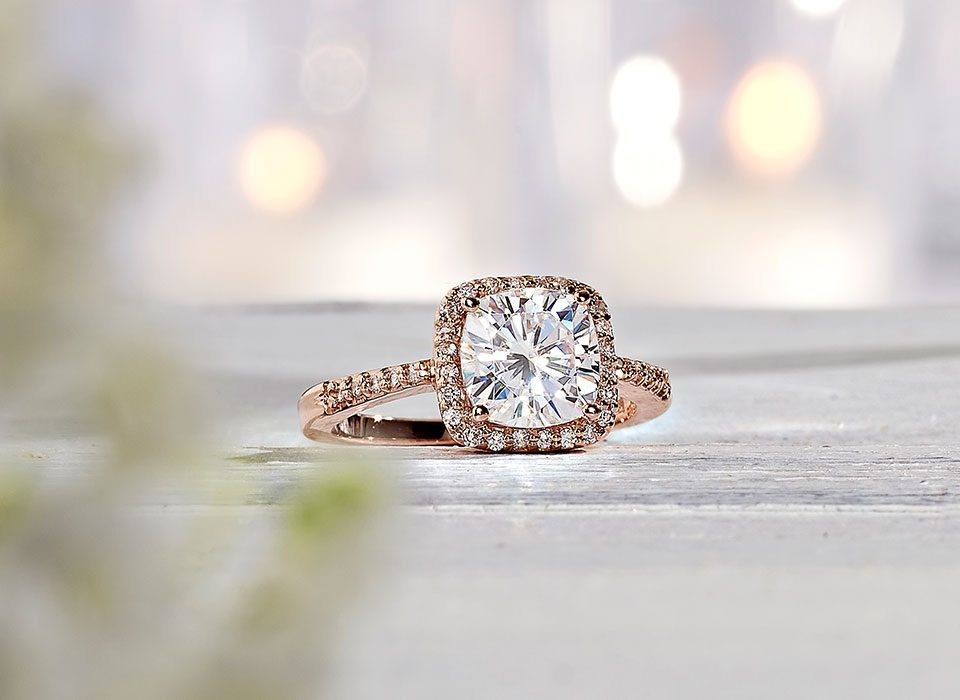 A cushion cut moissanite ring with halo and pave setting with a rose gold band