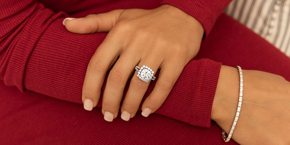A hand wearing a cushion cut with halo setting moissanite engagement ring