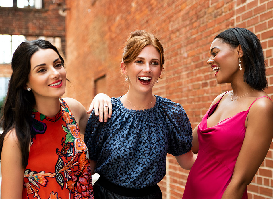 Three women laughing while wearing moissanite jewelry